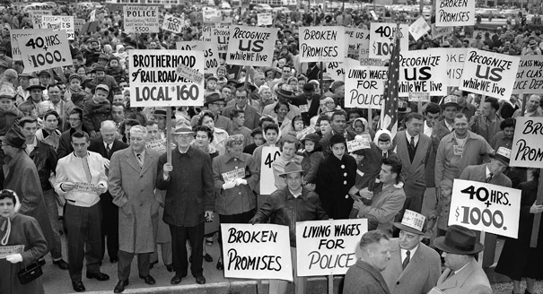 Police and firemen, some with their wives and children, assemble on Philadelphia's Rayburn Plaza, Nov. 13, 1956 to carry their wages and hours demand to City Council. The police and firemen are demanding an increase of $1,000 a year and a 40-hour week. (AP Photo/Sam Myers)